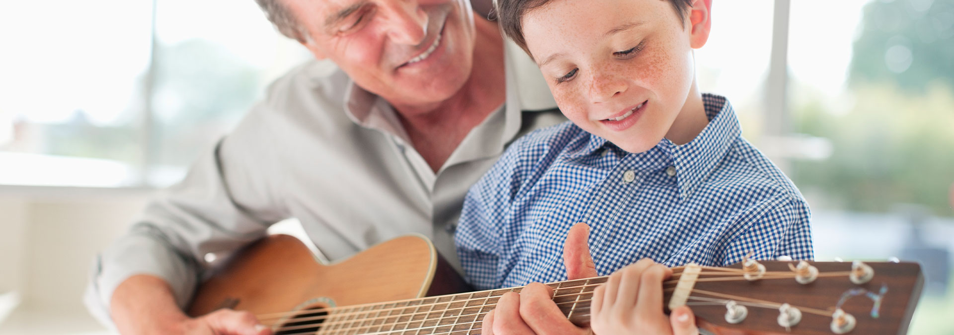 Grandfather and grandson playing the guitar